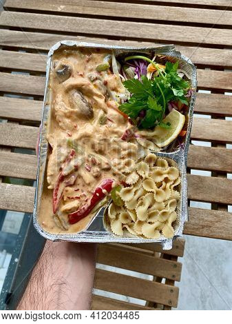 Take Away Creamy Cajun Chicken, Pasta And Salad In Take Out Foil Food Plate. Holding In Hand. Ready