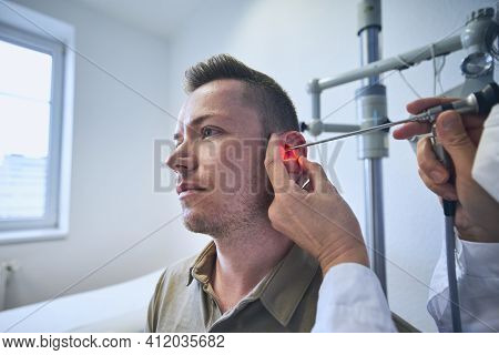 Patient At Ent Clinic. Specialist Doctor - Otolaryngologist Doing Ear Examination Of Young Man.