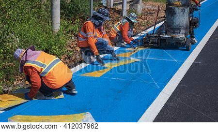 Road Workers Group In Reflective Vests With Thermoplastic Spray Road Marking Machine Are Working To