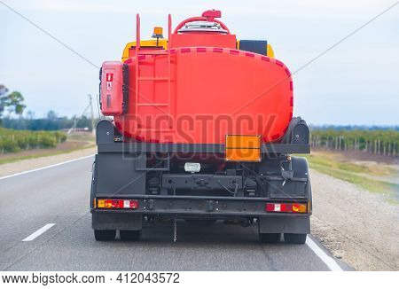Gasoline Tanker Is Moving On A Single-lane Country Road. Back View.