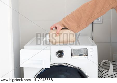Woman's Hand Putting Detergent Into The Washing Machine.concept Of Cleanliness At Home
