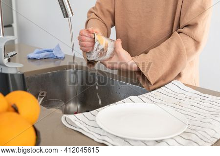 Woman Scrubbing A Dirty Glass With A Yellow Scouring Pad Under A Kitchen Faucet