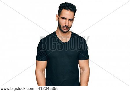 Hispanic man with beard wearing casual black t shirt skeptic and nervous, frowning upset because of problem. negative person.