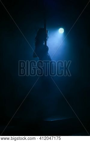 Striptease In Night Club. Caucasian Girl In The Spotlight In A Swimsuit, Heels, On Stage With A Pole