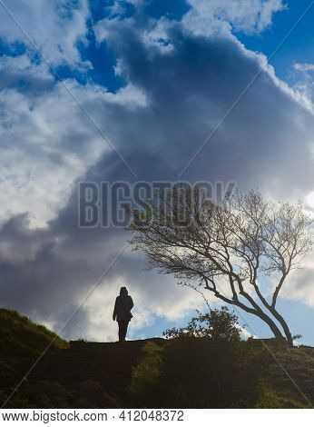 Girl Walks In Windy Weather Over Hilly Terrain Under Cumulus Clouds.