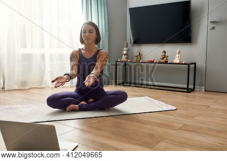 Girl Stretching Out Her Arms Forward While Sitting On A Sports Mat At Home. Girl In Sportswear Leadi