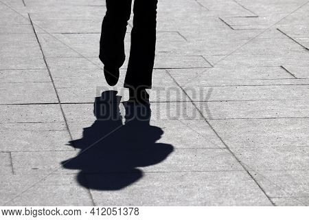 Silhouette And Shadow Of Slim Woman Walking On A Street. Concept Of Loneliness, Slimming, Human Life