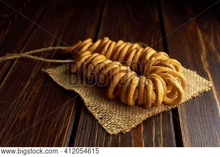 Wheat Bagels On A Rope On Burlap Cloth On Dark Wooden Table. Traditional Russian Food.
