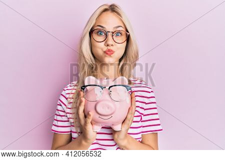 Beautiful caucasian blonde girl holding piggy bank with glasses puffing cheeks with funny face. mouth inflated with air, catching air.