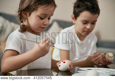 Charming Little Girl With Braids Wearing White T-shirt,sitting Next To Her Brother, Uses Paintbrush