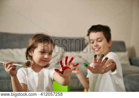 Two Happy Children Showing Their Hands Smeared With Colored Paints To The Camera During Coloring Egg