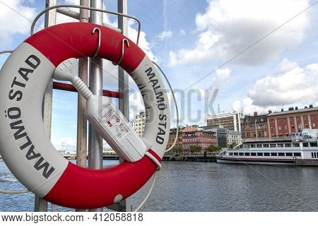 Lifeguard On Pole Next To The Port Of Entry To The City Of Malmo (sweden) With Background Of Ship An