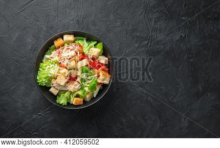 Classic Caesar Salad With Crispy Crackers On A Dark Background. Top View With Copy Space. The Concep
