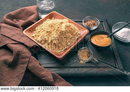 Mustard Powder, Ready-made Mustard, Salt, Spices And Water On A Brown Background. Side View, Horizon