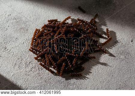 Organic Uncooked Buckwheat Fusilli Pasta On Grey Stone Background. Wholegrain Gluten Free Noodles. H