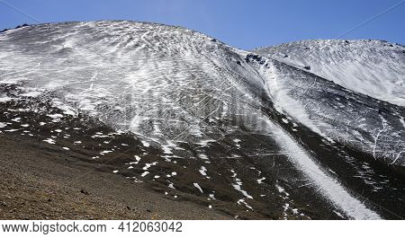 Background Dark Mountain Sprinkled With White Snow With Trails And Footprints. A Rocky, Loose Mounta