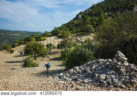Hiking Lycian way. Man is walking on dry stony highland on stretch between Kalkan and Kas of Lycian way trail, Trekking in Turkey, outdoor activity