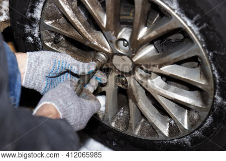 Mens Hands In Gray Gloves Unscrew Bolts From The Dirty Wheel Of The Machine.