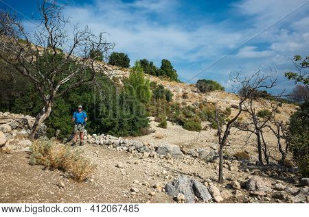 Hiking Lycian way. Man is standing on dry stony highland under dead tree on stretch between Kalkan and Kas of Lycian way trail, Trekking in Turkey, outdoor activity