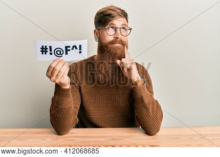 Young irish redhead man holding paper with insult message sititng on the table serious face thinking about question with hand on chin, thoughtful about confusing idea