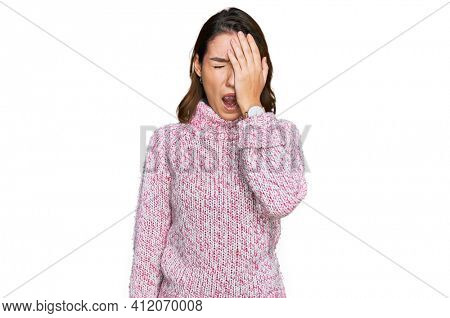 Young caucasian girl wearing wool winter sweater yawning tired covering half face, eye and mouth with hand. face hurts in pain.