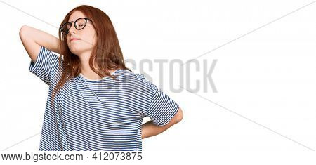 Young read head woman wearing casual clothes and glasses suffering of neck ache injury, touching neck with hand, muscular pain