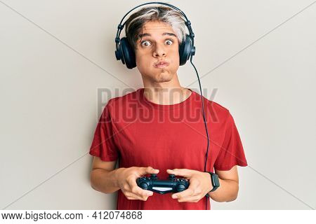 Young hispanic man playing video game holding controller puffing cheeks with funny face. mouth inflated with air, catching air.