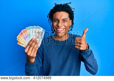 Young african american man holding swiss franc banknotes smiling happy and positive, thumb up doing excellent and approval sign