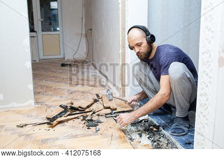 A Worker Dismantles The Old Parquet Floor With A Hammer And Chisel. Renovation In The Apartment