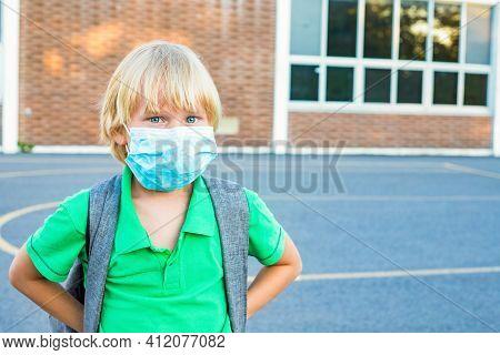 Child In Face Mask Near School During Corona Virus Outbreak.