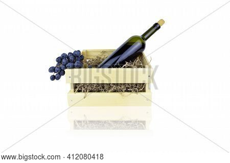 Bottle Of Red Wine With Cork And Bunch Of Grapes In Wooden Box With Paper Shavings, Isolated On Whit
