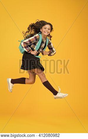 Enjoy School Holidays. Happy Girl Run From School. Little Child In Midair Yellow Background. School