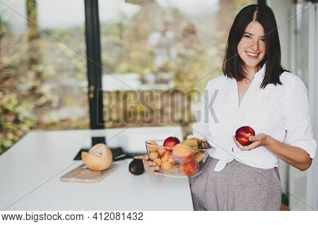 Young Happy Woman Holding Bowl With Fruits At White Countertop In Modern Kitchen. Healthy Eating