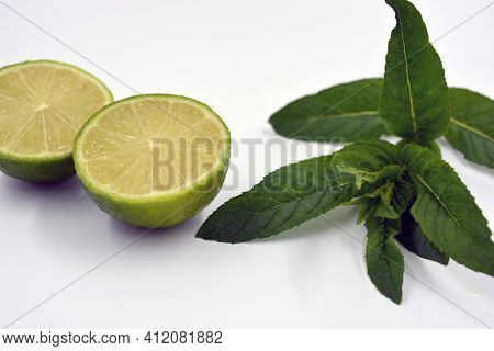 Healthy Ripe Delicious Fruits For Human Health. Juicy Fruits Of Green Lime With Green Lime Leaves. T