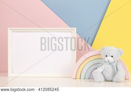 White Blank Wood Frame With Teddy Bear And Pastel Toy Rainbow On White Desk. Blank Horizontal Frame