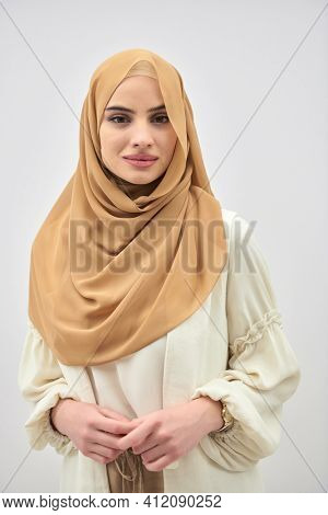 Portrait of young muslim woman wearing hijab on isolated white background