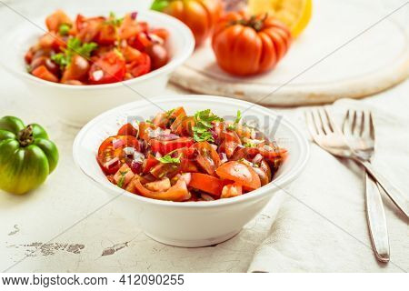 Mexican Pico de Gallo with ingredients - tomato salad, Mexica salsa with onion, parsley, coriander and lemon