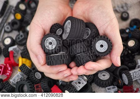 Tambov, Russian Federation - March 11, 2021 A Young Boy Holding A Handful Of Lego Wheels In His Hand