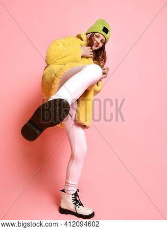 Bright Unruly Girl Kicks The Camera, Standing On A Pink Background. Aggressive Teenager In A Green H