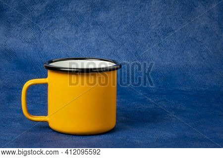 yellow metal enamel cup of tea on a blue textured paper background with a copy space