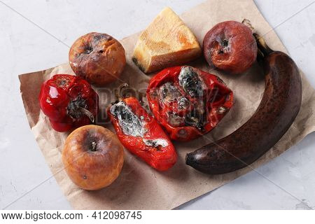 Spoiled Rotten Foods With Mold: Apples, Peppers, Hard Cheese And Banana On Gray Background