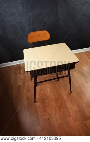 Empty wooden school chair and desk against a black chalkboard