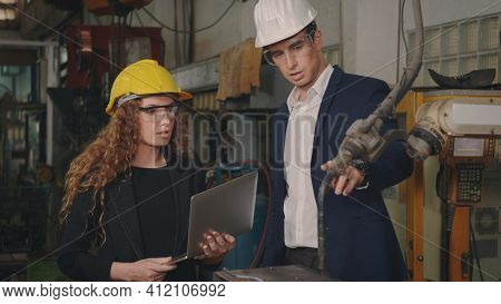 Caucasian Maintenance Engineer Man And Diverse Female Factory Workers In Hardhats Talking And Presen