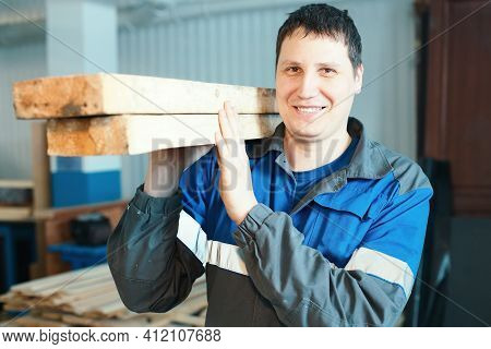 A Young Man Stands In A Carpentry Shop And Holds Wooden Bars On His Shoulder. A Sawmill Worker Carri