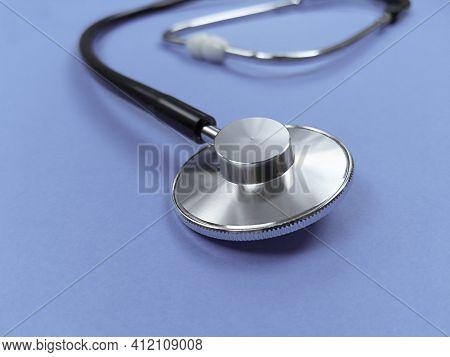 Black Stethoscope On Violet Background. Stock Photo.