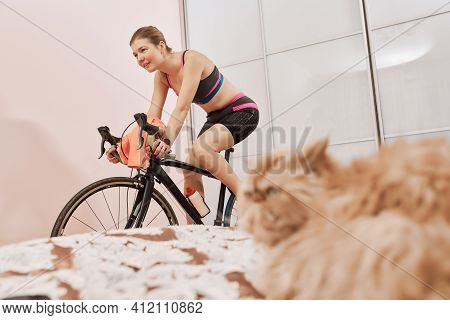 Woman Trains At Home On A Stationary Bike During A Pandemic. Concept Of Home Workout And Social Dist