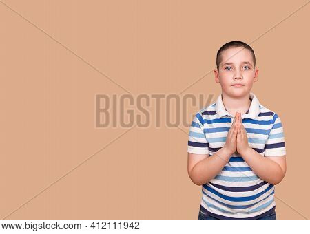 Calm Boy Praying To God With Hands Held Together. Little Boy Praying In The Morning. Portrait Of Kid