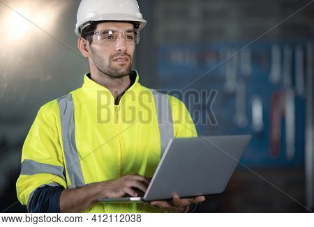 Chief Engineer In The Hard Hat Walks Through Light Modern Factory While Holding Laptop. Successful,