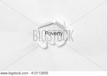 Word Poverty On White Isolated Background, The Inscription Through The Wound Hole In Paper. Concept