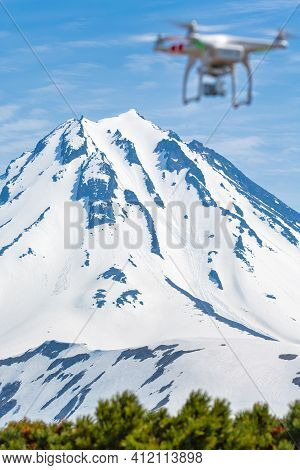 Snowcapped Winter Volcano Peak And Defocused Flying Uav Quadcopter Drone With Camera In Blue Sky Aer